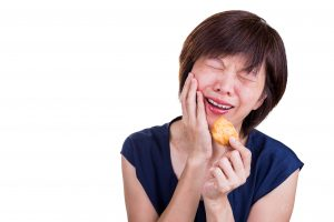 Asian women with intense toothache pain after biting cookie