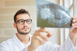 Zahnarzt schaut auf Röntgenbild