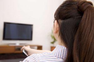 テレビのチャンネルを変えようとする女性