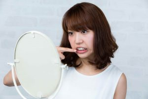 鏡・口元を気にする女性